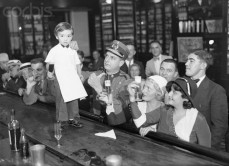 29 Dec 1931, Havana, Cuba --- 12/29/31-Havana, Cuba: Sloppy Joe, Jr., just four years of age and having two years behind the bar, is celebrating his graduation from apprenticeship by mixing his real champagne cocktail behind his father's world-famed bar. Sloppy Joe Jr., is quite proficient at mixing the more common varieties. Here, customers toast the little guy. --- Image by © Bettmann/CORBIS