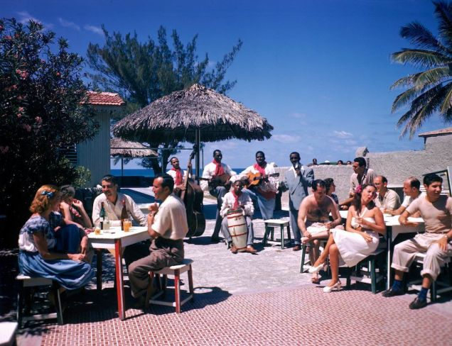 Guests-sit-at-outdoor-tables-in-the-Kastillito-Club-and-talk-together-while-a-band-performs-in-Varadero-Cuba.